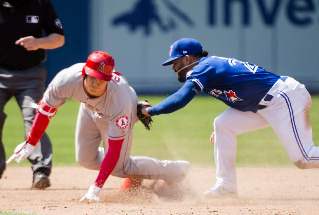 Los Angeles Angels designated hitter Shohei Ohtani (17) slides safely past Toronto Blue Jays second baseman Devon Travis (29) after hitting a double during the ninth inning of a baseball game in Toronto, Thursday, May 24, 2018. (Nathan Denette/The Canadian Press via AP)