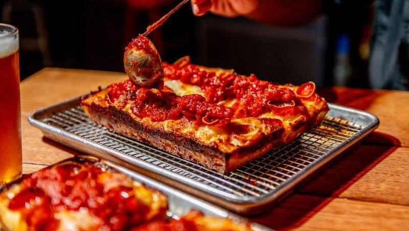 detroit style pizza being sauced