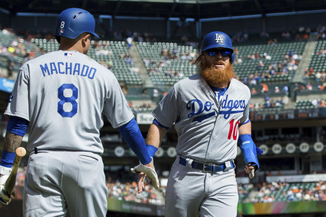 Los Angeles Dodgers Justin Turner, right, celebrates with Manny Machado after scoring a run against the San Francisco Giants in the first inning of a baseball game in San Francisco, Sunday, Sept. 30, 2018. (AP Photo/John Hefti)