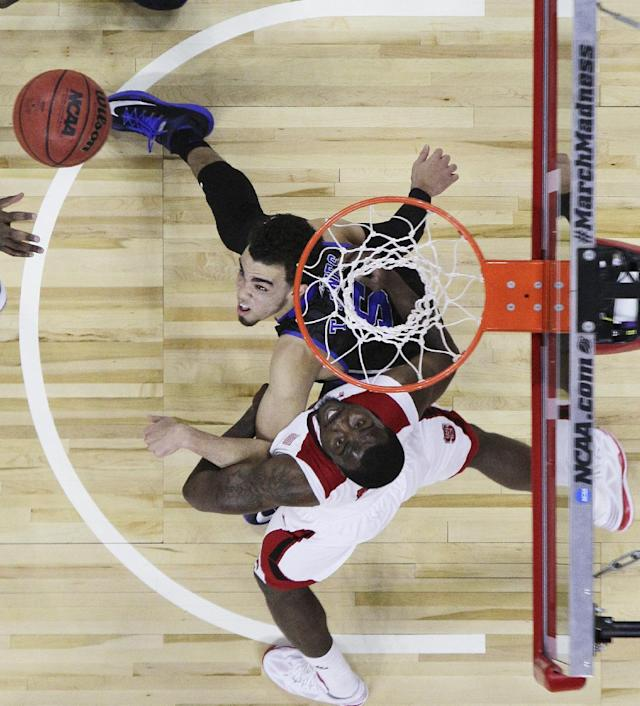 Duke's Tyus Jones, top, and North Carolina State's Desmond Lee struggle for a rebound during the first half of an NCAA college basketball game in Raleigh, N.C., Sunday, Jan. 11, 2015. North Carolina State won 87-75. (AP Photo/Gerry Broome)