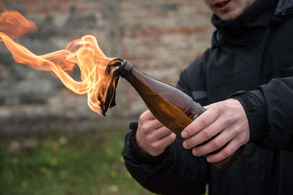Man holding a lit Molotov cocktail