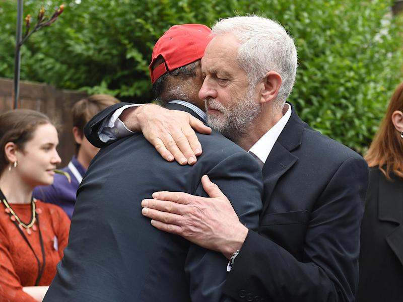 Labour leader Jeremy Corbyn hugs councillor Mushtaq Lasharie as he arrives at St Clement's Church in Latimer Road, where volunteers have provided shelter and support for people affected by the fire at Grenfell Tower (Getty)