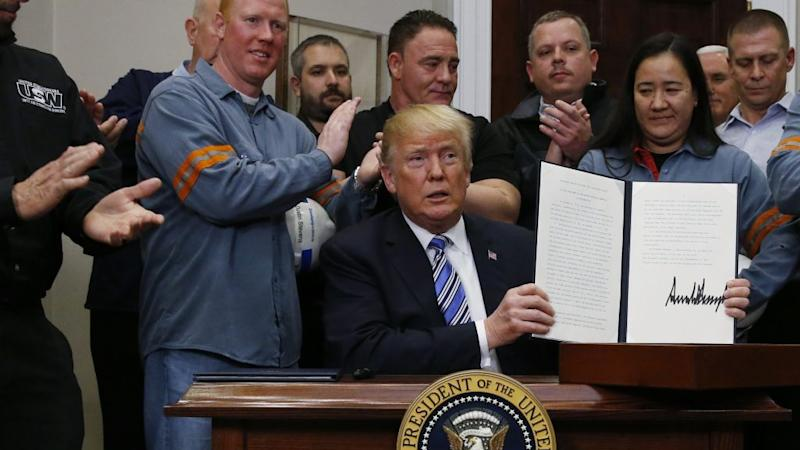 U.S. President Donald Trump holds up a proclamation during a White House ceremony to establish tariffs on imports of steel and aluminum at the White House in Washington, U.S., March 8, 2018.