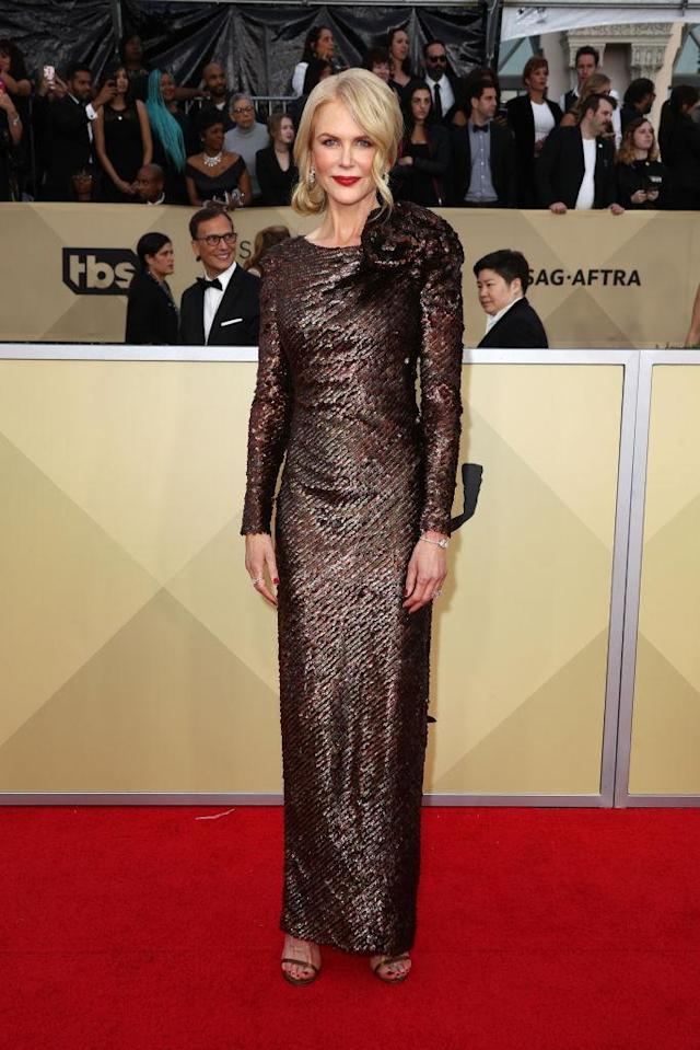 <p>The Australian actress made an entrance onto the red carpet in a shimmering bronze dress and bold red lip. (Photo: Getty Images) </p>