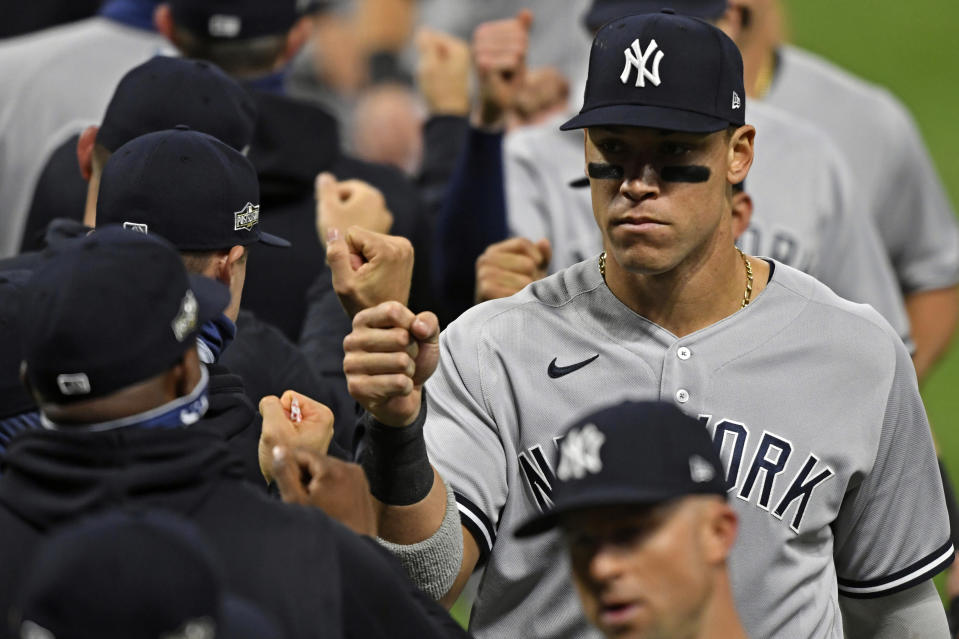 New York Yankees' Aaron Judge (99) gets a fist bump after the Yankees defeated the Cleveland Indians 12-3 in Game 1 of an American League wild-card baseball series, Tuesday, Sept. 29, 2020, in Cleveland. (AP Photo/David Dermer)