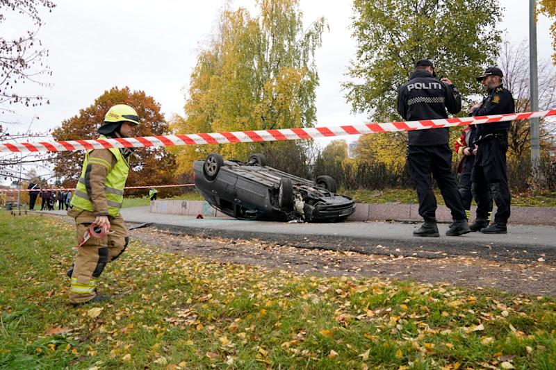 An upturned car is cordoned off by police after an incident in the centre of Oslo (AP)