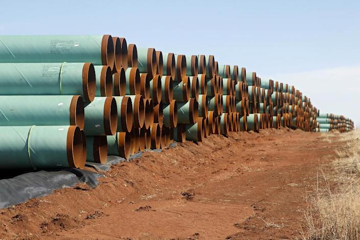 """FILE - In this Wednesday, Feb. 1, 2012 file photo, miles of pipe ready to become part of the Keystone Pipeline are stacked in a field near Ripley, Okla. President Barack Obama says that the proposed Keystone XL pipeline project from Canada to Texas should only be approved if it doesn't worsen carbon pollution. Obama says allowing the oil pipeline to be built requires a finding that doing so is in the nation's interest. He says that means determining that the pipeline does not contribute and """"significantly exacerbate"""" emissions. (AP Photo/Sue Ogrocki, File)"""