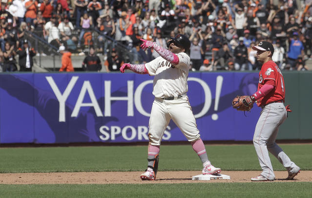 San Francisco Giants' Pablo Sandoval, center, gestures after hitting a double against the Cincinnati Reds during the eighth inning of a baseball game in San Francisco, Sunday, May 12, 2019. At right is Reds shortstop Jose Iglesias. (AP Photo/Jeff Chiu)