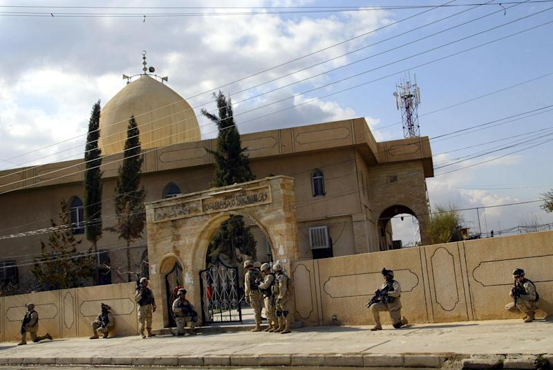US soldiers take position in front of a mosque in Mosul on February 11, 2005