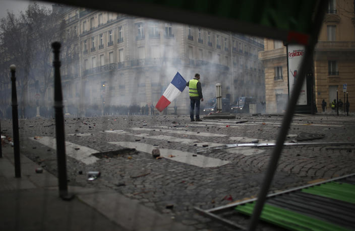 A demonstrators stands alone with a French flag during clashes Saturday, Dec. 8, 2018 in Paris. (Photo: Rafael Yaghobzadeh/AP)