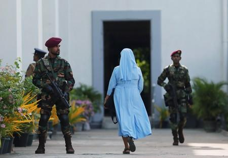 FILE PHOTO: A nun arrives as a Sri Lanka's commando soldier stands guard in front of the main entrance to St. Lucia Cathedral as survivors and families of victims of Sri Lanka's Easter Sunday bombing arrive for a special mass for those who lost their lives