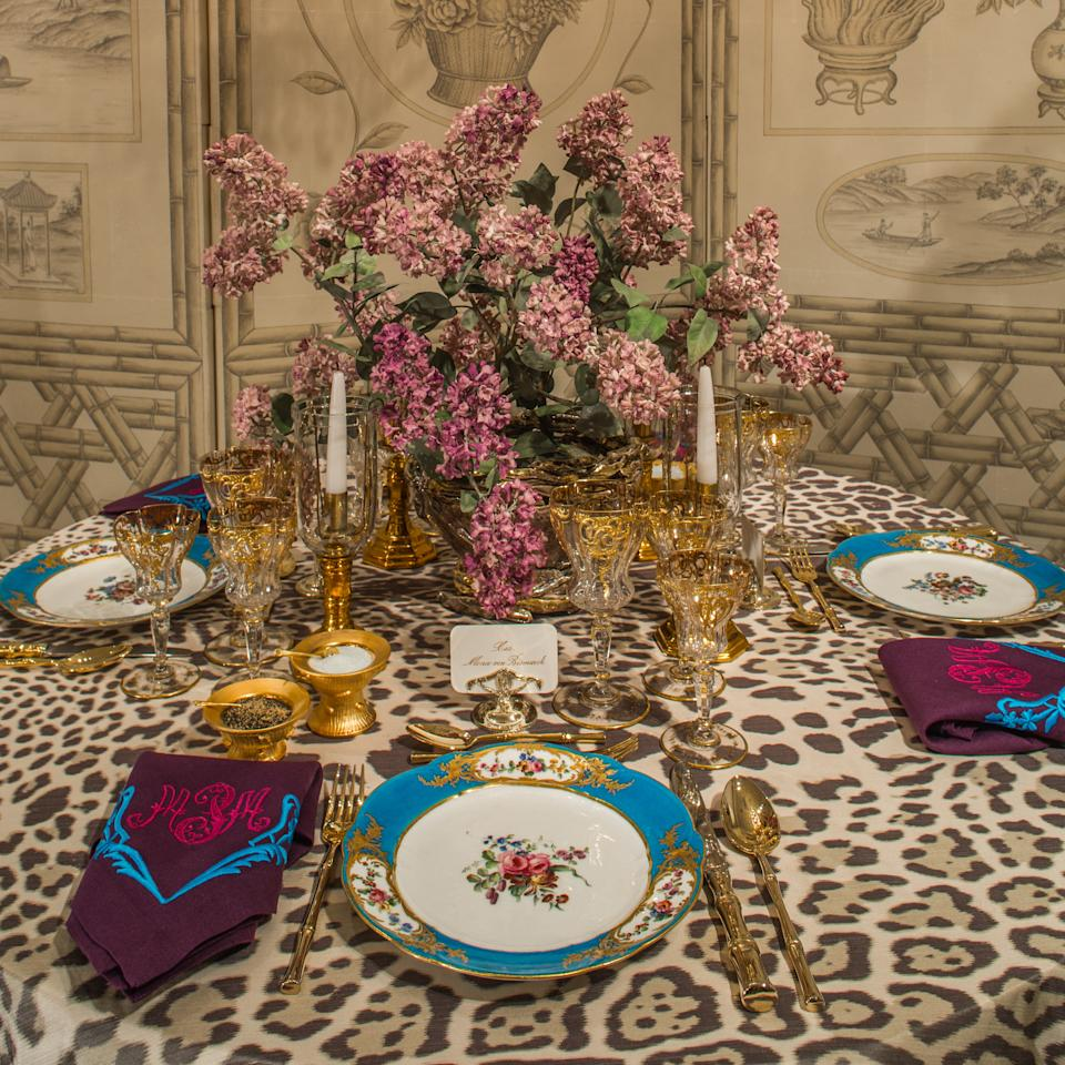 """""""I wanted it to be a little bit of Marjorie gone current and modern,"""" Papachristidis says of his table, whose pops of color stem from the floral porcelain he selected from her collection. """"So I took a neutral palette and then had Vlad [<a rel=""""nofollow"""" href=""""https://www.architecturaldigest.com/story/vladimir-kanevsky-incredible-floral-sculptures-take-over-the-hermitage-saint-petersburg?mbid=synd_yahoo_rss"""">Kanevsky</a>, the master of porcelain flora] make the flowers. I felt if Marjorie was around today she'd do something fab like Vladimir, who of course is Russian. If Marjorie had known him, these flowers would have been all around Hillwood."""" Indeed, much of Papachristidis's design hinged on what Marjorie would have done if she were around today. """"I approached it as if we were collaborating,"""" he says. That included using his usual go-to sources, in addition to Kanevsky: Christopher Spitzmiller created custom gold salt cellars, Leontine Linens embroidered napkins, and Papachristidis pulled fabric from his own personal collection to serve as the tablecloth. There was a fair bit of fantasy involved too, though: the guests noted on Post's gold-plated place card holders? Post, Pauline de Rothschild, the Duchess of Windsor, and Mona von Bismarck. """"My gals!"""" exclaims Papachristidis gleefully. """"I mean, that's a pretty good group, right?"""""""