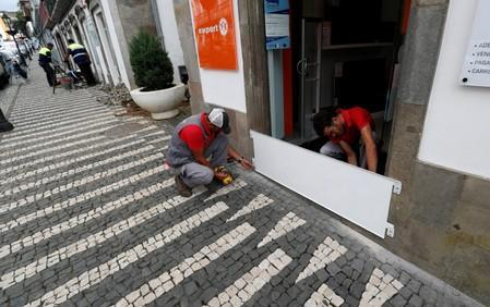 Two workers install a protection board before the arrival of Hurricane Lorenzo in Angra do Heroismo in the Azores islands