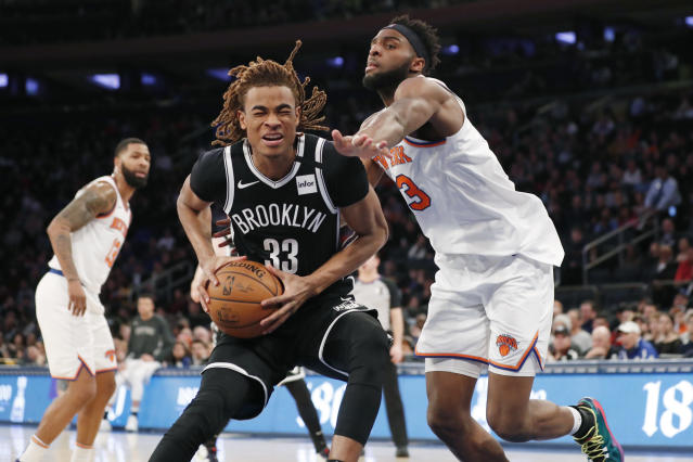 New York Knicks center Mitchell Robinson (23) defends Brooklyn Nets forward Nicolas Claxton (33) during the second half of an NBA basketball game in New York, Sunday, Jan. 26, 2020. The Knicks defeated the Nets 110-97. (AP Photo/Kathy Willens)