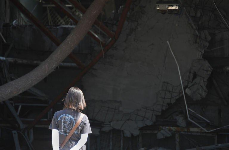 A tourist looks at debris inside a damaged building at a devastated area in Rikuzentakata, Japan, on July 20, 2013