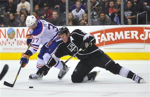 Edmonton Oilers' Lennart Petrell, left, of Finland, vies for the puck with Los Angeles Kings defenseman Matt Greene during the first period of an NHL hockey game, Monday, April 2, 2012, in Los Angeles. (AP Photo/Richard Hartog)
