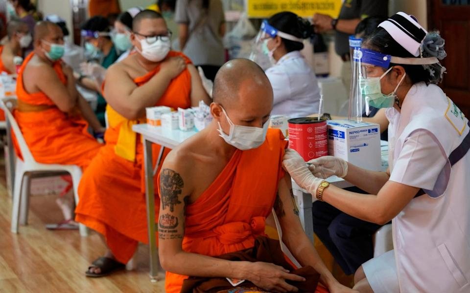 Health workers administer doses of the AstraZeneca vaccine to Buddhist monks at the Wat Srisudaram in Bangkok - AP