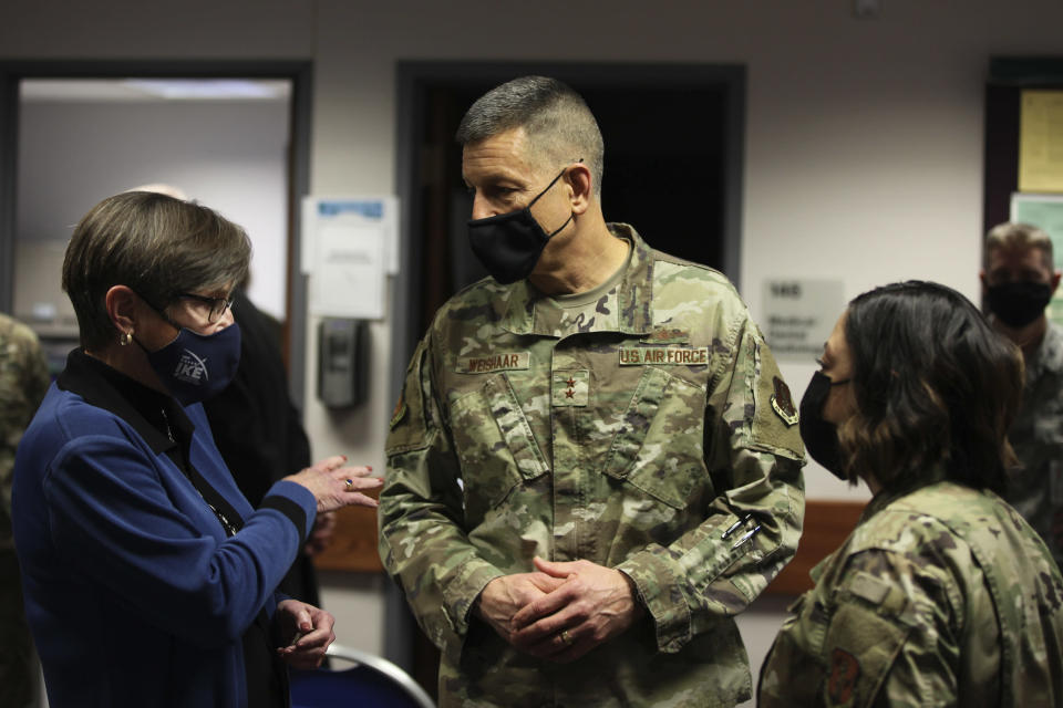 Kansas Gov. Laura Kelly, left, confers with Maj. Gen. David Weishaar, center, and Capt. Ana Tavares, right, during a COVID-19 vaccine clinic for Kansas National Guard personnel, Friday, Feb. 5, 2021, at Air National Guard's base south of Topeka, Kan. Weishaar is the Kansas National Guard's commanding officer and the state's top emergency management official. (AP Photo/John Hanna)