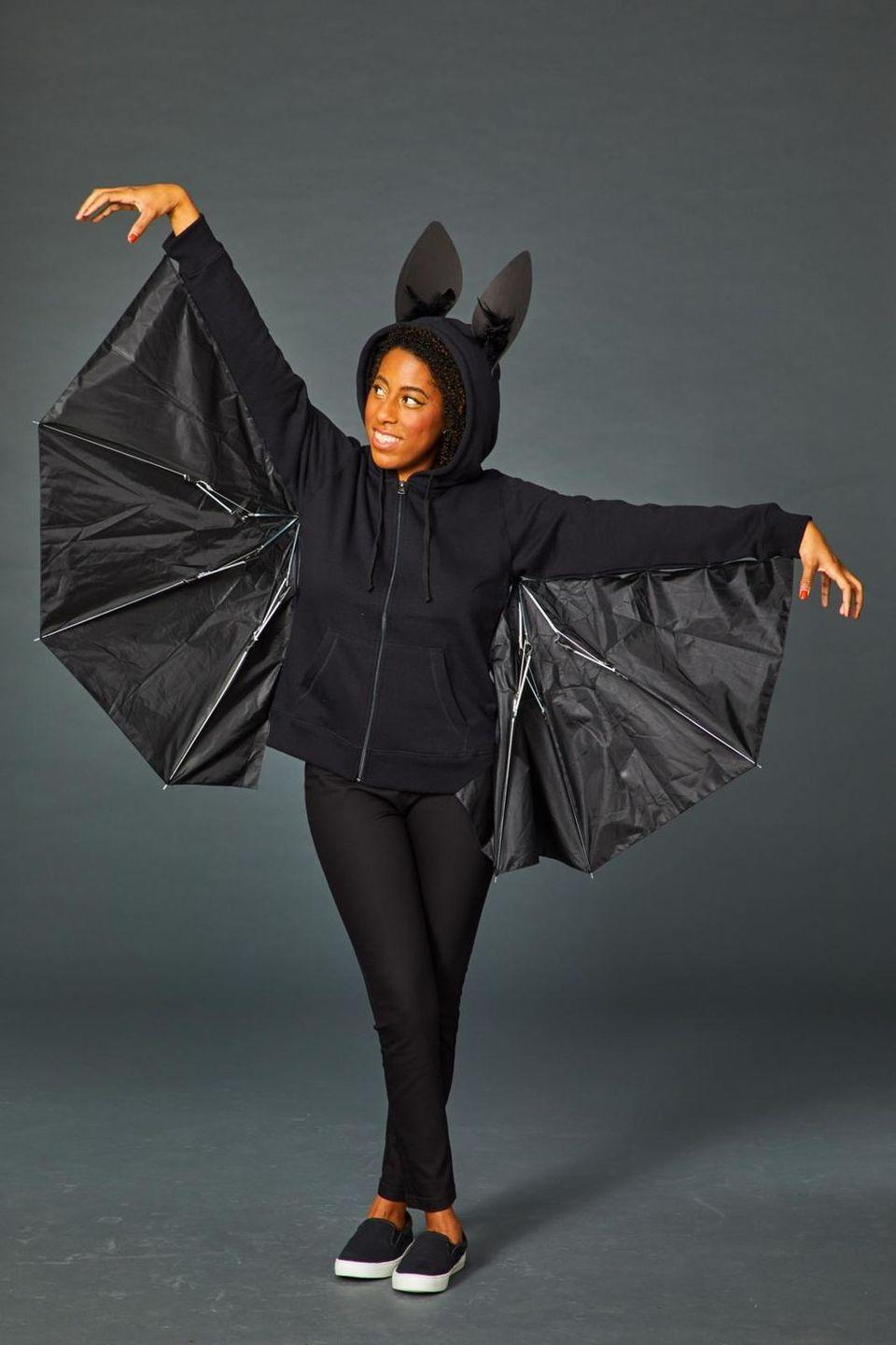"""<p>Give new life to a broken umbrella with this clever costume. To make, cut that broken umbrella in half and use black safety pins or hot glue to attach it to the arms of a black hoodie. Fasten the hinges of the umbrella pieces with black electrical tape, so you can open your wings to get the full bat effect. Then finish off your look with black foam ears dotted with black feathers.</p><p><a class=""""link rapid-noclick-resp"""" href=""""https://www.amazon.com/Hanes-Womens-Jersey-Hoodie-Medium/dp/B016YKIBS2?tag=syn-yahoo-20&ascsubtag=%5Bartid%7C10070.g.490%5Bsrc%7Cyahoo-us"""" rel=""""nofollow noopener"""" target=""""_blank"""" data-ylk=""""slk:SHOP BLACK HOODIES"""">SHOP BLACK HOODIES</a></p>"""