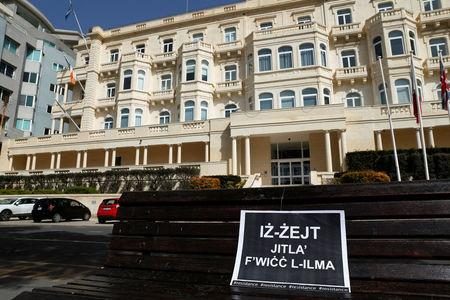 """A placard with a Maltese idiom reading: """"The truth will always surface"""" is seen outside Whitehall Mansions, which houses the Maltese-registered Pilatus Bank, in Ta' Xbiex, Malta March 21, 2018. REUTERS/Darrin Zammit Lupi"""