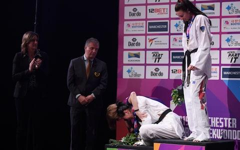 Zheng dropped to her knees both in the ring and on the podium - Credit: GETTY IMAGES