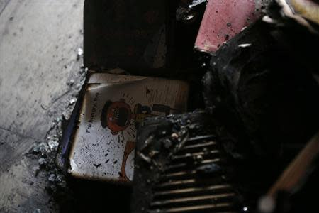 An English textbook is seen among debris at a dining room of a migrant shelter destroyed by an arson attack in Seoul October 14, 2013. REUTERS/Kim Hong-Ji
