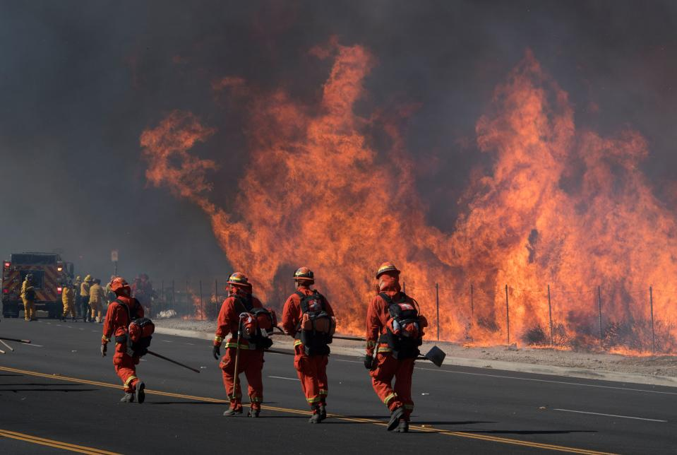 "Inmate firefighters (in orange) prepare to put out flames on the road leading to the Reagan Library during the Easy Fire in Simi Valley, California on October 30, 2019. - Firefighters in California battled a new fast-moving blaze on Wednesday that threatened the Ronald Reagan Presidential Library, as rare ""extreme"" red flag warnings were issued for much of the Los Angeles region. The so-called Easy Fire in the Simi Valley northwest of Los Angeles erupted around 6:00 am, forcing the evacuation of the library and nearby homes as it spread to more than 900 acres (365 hectares), officials said. (Photo by Mark RALSTON / AFP) (Photo by MARK RALSTON/AFP via Getty Images)"