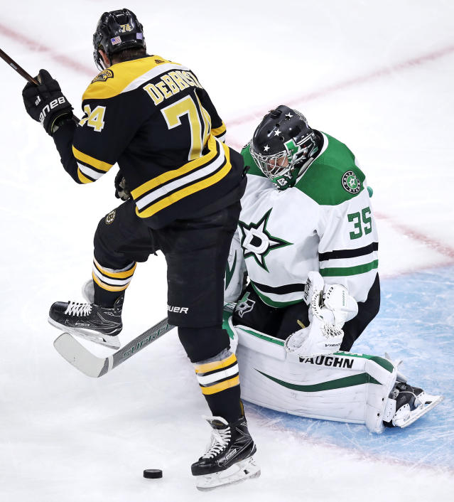 Boston Bruins left wing Jake DeBrusk (74) steps out of the path of the puck as Dallas Stars goaltender Anton Khudobin (35) makes a save during the first period of a hockey game in Boston, Monday, Nov. 5, 2018. (AP Photo/Charles Krupa)