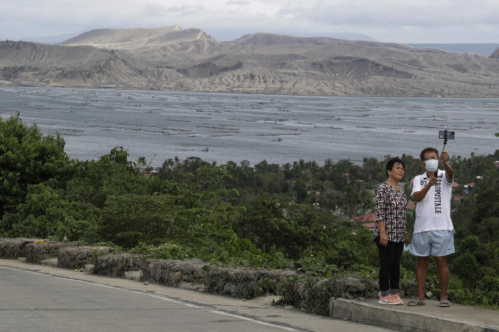 A couple poses for a selfie with the Taal volcano in background almost a year after it erupted on Sunday, Jan. 10, 2021 in Batangas province, Philippines. A popular tourist destination just south of Manila because of its picturesque setting in the middle of a lake, Taal erupted on Jan. 12, 2020. The eruption displaced thousands of villagers living near the area and delivered an early crisis this year for one of the world's most disaster-prone nations a couple of months before the COVID-19 pandemic broke in the country. (AP Photo/Aaron Favila)