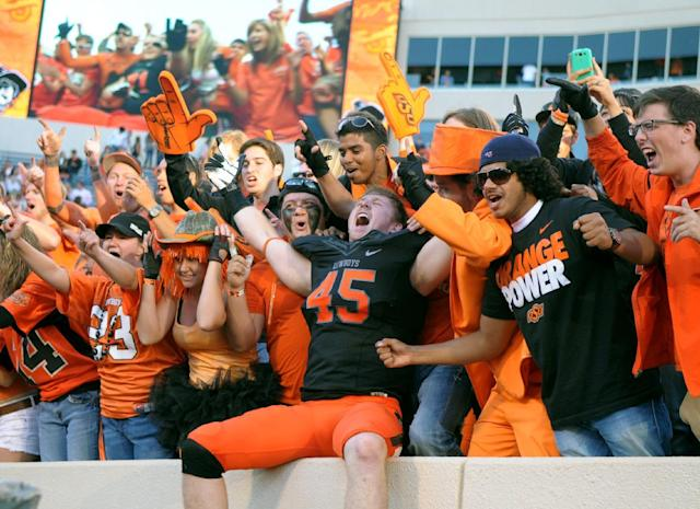 Oklahoma State linebacker Caleb Lavey celebrates with fans following an NCAA football game against Kansas State in Stillwater, Okla., Saturday, Oct. 5, 2013. Oklahoma State won 33-29. (AP Photo/Brody Schmidt)