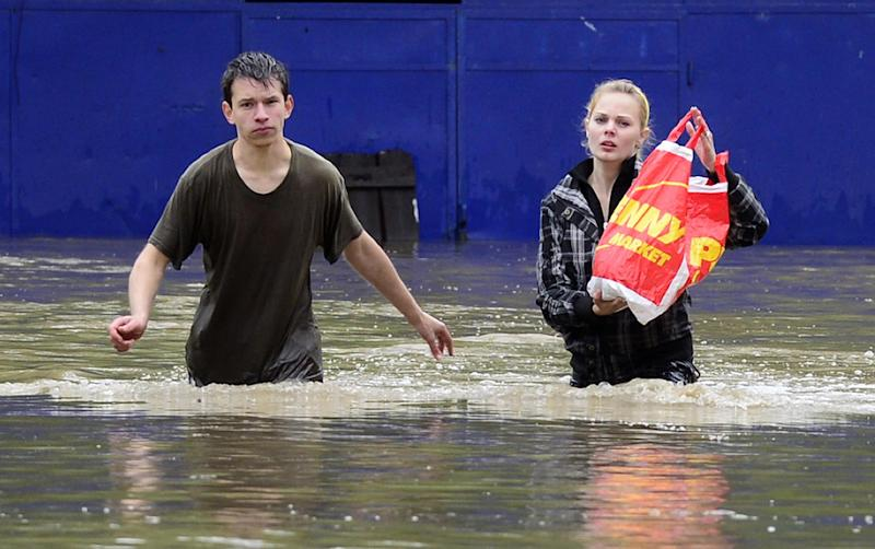 The Sunday, June 2, 2013 photo shows a couple trying to save three small kittens hidden in a plastic bag, which were endangered by a swollen Botic creek in Prague's suburb Zabehlice, Czech Republic, on Sunday, June 2, 2013. (AP Photo/CTK, Roman Vondrous) SLOVAKIA OUT