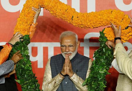 Indian Prime Minister Narendra Modi gestures as he is presented with a garland by Bharatiya Janata Party (BJP) leaders after the election results in New Delhi, India, May 23, 2019. REUTERS/Adnan Abidi