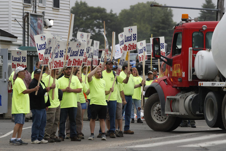 Striking shipbuilders pause their march to allow a truck to enter Bath Iron Works, Monday, June 22, 2020, in Bath, Maine. Production workers rejected the company's three-year contract offer Sunday, threatening to further delay delivery of ships. (AP Photo/Robert F. Bukaty)