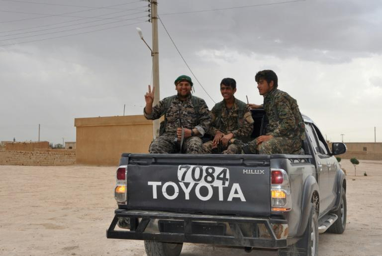 Fighters from the Syrian Democratic Forces sit in a pick-up truck near Tishreen Farms, on the northern outskirts of Raqa on May 2, 2017, after they pushed their way to within 17 kilometres (10 miles) north of the Islamic State group's stronghold