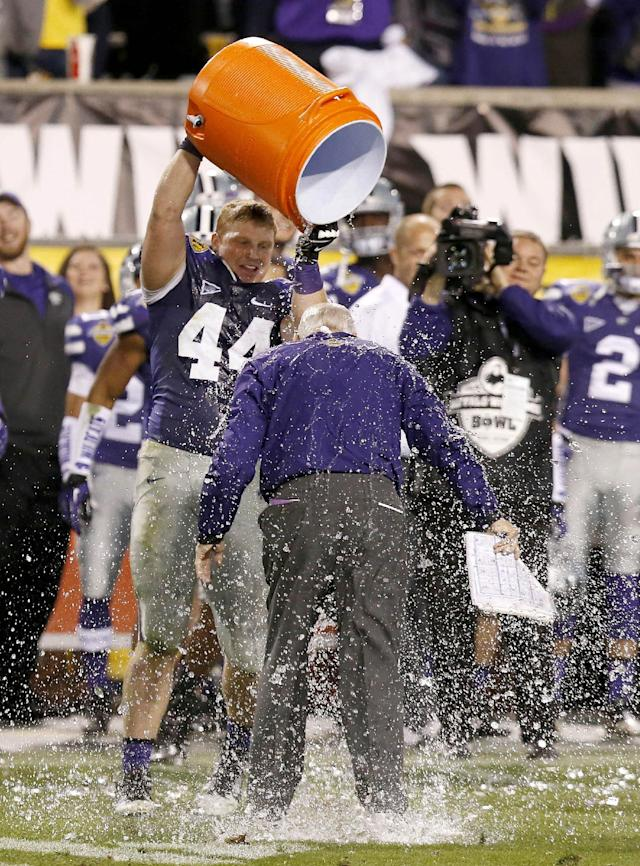 Kansas State's Ryan Mueller (44) gets Kansas State head coach Bill Snyder drenched as they celebrate in the closing moments of the Buffalo Wild Wings Bowl NCAA college football game against Michigan, Saturday, Dec. 28, 2013, in Tempe, Ariz. Kansas State defeated Michigan 31-14. (AP Photo/Ross D. Franklin)