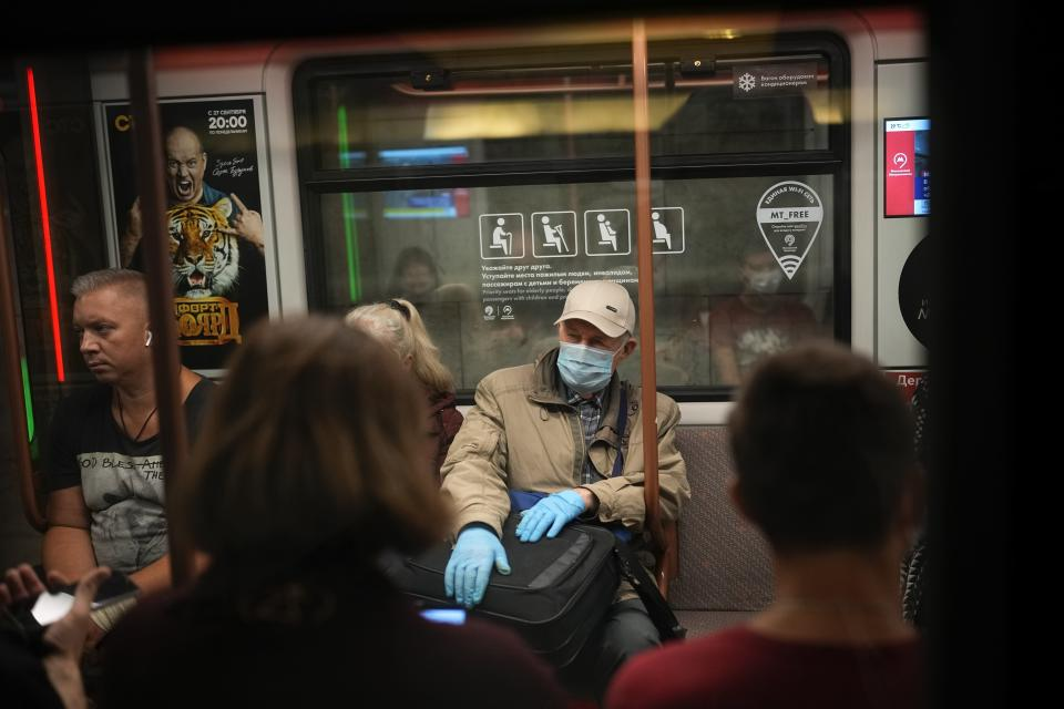 """FILE - In this Sept. 12, 2021, an elderly man wearing a face mask and gloves to protect against the coronavirus rides a subway car in Moscow, Russia. When Russians discuss the coronavirus -- from ordinary conversations to remarks even by President Vladimir Putin -- the talk often turns to """"antitela."""" That's the Russian word for antibodies — the proteins produced by the body to fight infection. (AP Photo/Alexander Zemlianichenko, File)"""