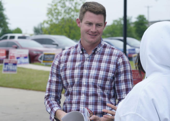 Texas congressional candidate Michael Wood, left, smiles as he listens to potential voter Yvette Williams outside an early voting location Tuesday, April 27, 2021, in Mansfield, Texas. Wood is considered the anti-Trump Republican Texas congressional candidate that Illinois Congressman Adam Kinzinger has endorsed in the May 1st special election for the 6th Congressional District. (AP Photo/LM Otero)