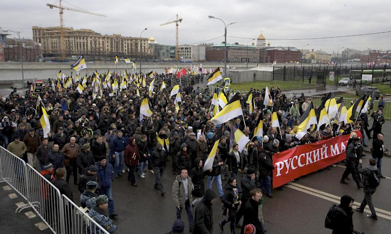 """Ultra nationalist demonstrators and activists shout anti-government slogans, with banner reading """" Russian March"""", as they march to mark National Unity Day, in Moscow, on Sunday, Nov. 4, 2012. The march took place on Unity Day, a national holiday established in 2005 to replace commemorations of Bolshevik Revolution. (AP Photo/Ivan Sekretarev)"""