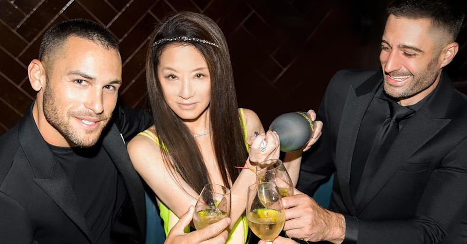 Vera Wang with two men dressed in black