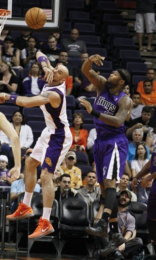 Phoenix Suns' Marcin Gortat, left, of Poland, passes the ball off as Sacramento Kings' DeMarcus Cousins, defends during the first half of an NBA preseason basketball game, Monday, Oct. 22, 2012, in Phoenix. (AP Photo/Ross D. Franklin)