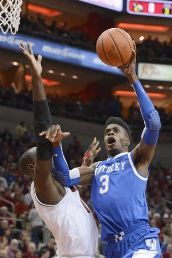 Kentucky's Nerlins Noel, right, gets a shot off over the defense of Louisville's Gorgui Dieng during the first half of an NCAA college basketball game Saturday, Dec. 29, 2012, in Louisville, Ky. (AP Photo/Timothy D. Easley)