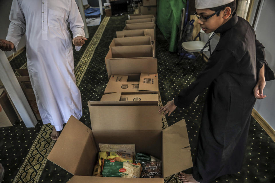 In this Wednesday, April 22, 2020, photo, Imam Mufti Mohammed Ismail, leader of An-Noor Cultural Center and masjid that serves a mostly Bangladeshi Muslim community in the Elmhurst neighborhood in the Queens borough of New York, and his son Hassan, 13, right, itemize boxes of food for distribution to those impacted by COVID-19 restrictions. Ismaill says this gives the center the opportunity to fulfill one of Ramadan's tenets — to serve those less fortunate, regardless of religion.. (AP Photo/Bebeto Matthews)
