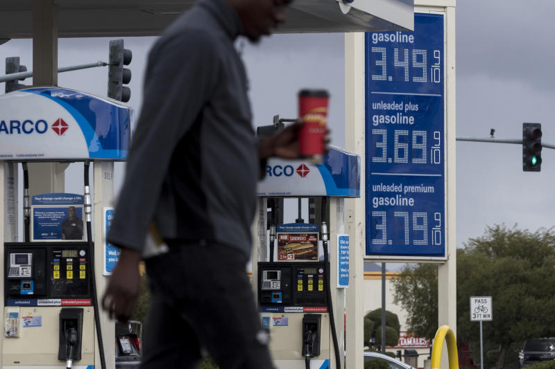 FILE - In this Nov. 29, 2018, file photo, a person walks past a gas station around Victorville, Calif. The average U.S. price of regular-grade gasoline has dropped 12 cents a gallon (3.8 liters) over the past three weeks to $2.31. Industry analyst Trilby Lundberg of the Lundberg Survey says Sunday, Jan. 13, 2019, that falling crude oil costs are the main reason for the decrease at the pump. The average gas price has dropped 66 cents over the past 3 ½ months. The highest average price in the nation is $3.46 a gallon in the San Francisco Bay Area. The lowest average is $1.80 in Baton Rouge, La. (James Quigg/The Daily Press via AP, File)