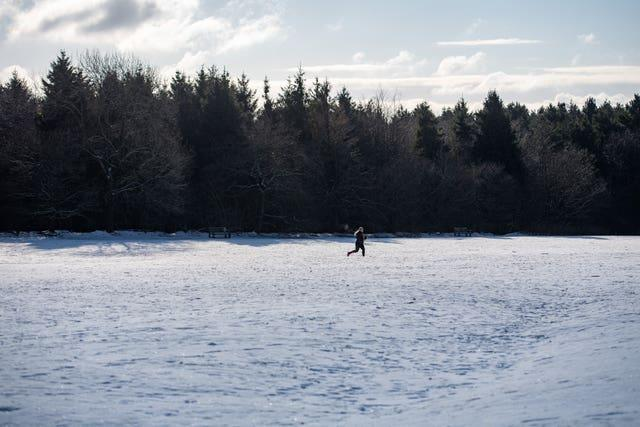 A runner navigates snow and ice at Lickey Hills Country Park in Birmingham