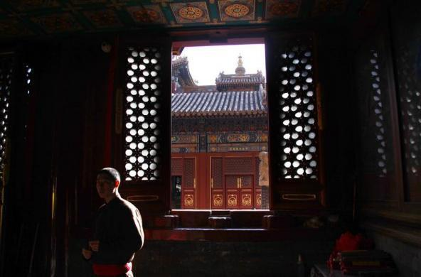 A monk watches devotees pray at one of the many small temples at the Yonghegong Lama Temple complex in central Beijing January 2, 2012.