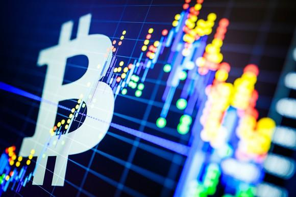 Bitcoin symbol superimposed on a candlestick chart in blue with yellow and red lights.