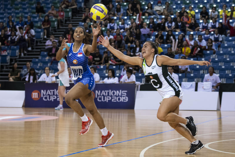 Singapore's Aqilah Andin (left) battles for the ball with Cook Islands' Maeva Carr during their Netball Nations Cup match at OCBC Arena. (PHOTO: Netball Singapore)