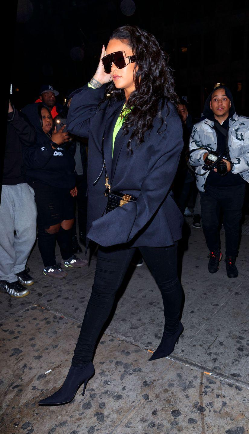 <p>In a neon green top under a baggy navy coat, black skinny pants, high heel boots, an on-trend waist bag, and oversized frames while out in NYC. </p>