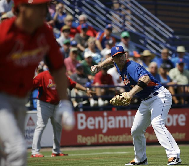 New York Mets' David Wright throws to first base after fielding a sacrifice bunt by St. Louis Cardinals' Peter Bourjos, left, in the first inning of an exhibition spring training baseball game, Wednesday, March 12, 2014, in Port St. Lucie, Fla. (AP Photo/David Goldman)