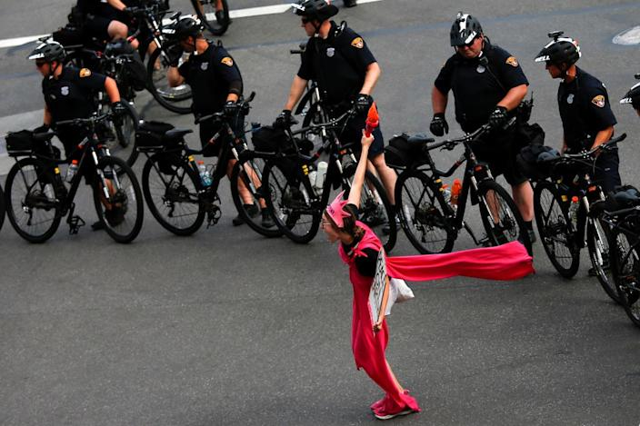 <p>An activist with Code Pink poses next to police on bicycles monitoring a protest march by various groups, including Black Lives Matter and Shut Down Trump and the RNC, ahead of the Republican National Convention in Cleveland, Ohio on July 17, 2016. (Photo: Adrees Latif/Reuters)</p>